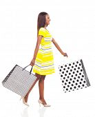 side view of happy afro american woman walking with shopping bags