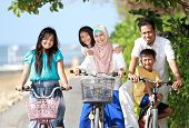 pic of muslim kids  - Portrait of happy muslim family with kids enjoy riding bicycle outdoor in the beach - JPG