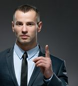 Portrait of making forefinger gesture man wears business suit and black tie