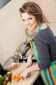 Pretty woman in striped apron slices vegetables in the modern comfortable kitchen