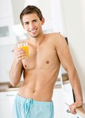 Half-naked man with glass of juice standing near the fridge at the kitchen