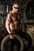 Handsome muscular man in the old garage.