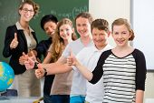 School class teacher and students stand in front of a blackboard with math work in a classroom durin