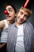 Two funny guys looking at camera and smiling crazily, fools day series