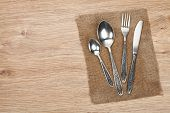 Silverware or flatware set of fork, spoon and knife on wooden table