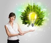 Young girl presenting idea light bulb with green tree concept