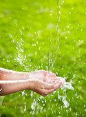 Stream of clean water pouring into children's hands.