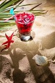 Raspberry cocktail on the sand on the beach
