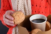 Woman holds box with coffee and cookies close-up