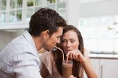 Close-up of a loving young couple sharing a drink at home
