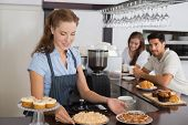 Female cafe owner holding sweet snacks with couple at counter in the coffee shop