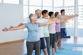 stock photo of senior class  - Portrait of fitness class stretching hands in row at yoga class - JPG