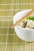 stock photo of wanton  - Close up vertical photo of freshly made wonton with chopsticks on top of white bowl