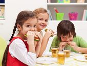 Three kids chomping on healthy sandwiches with cheese and vegetables