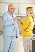 Woman offering a senior man a glass of water in the kitchen