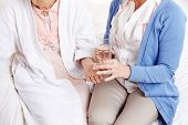 Senior citizen woman getting pill with water from a nurse