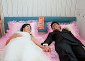 Bride And Groom Hold Their Hand And Lay On The Bed As Chinese Traditional