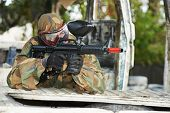 picture of paintball  - Adrenalin paintball player in protective uniform and mask aiming gun before shooting in summer - JPG