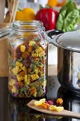 Large Storage Jar With Colorful Pasta And Cooking Spoon
