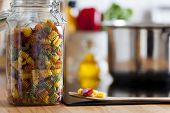 Close Up View Of An Open Storage Jar With Colorful Pasta
