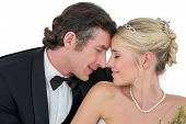 Affectionate bride and groom with head to head over white background