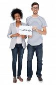 Full length portrait of a smiling couple holding a thank you note over white background
