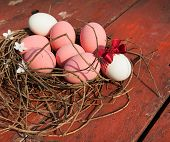 pink easter eggs on the table red nest