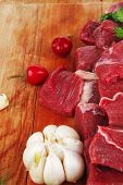 uncooked fresh beef meat chunks on wooden cutting plate with green hot and red peppers isolated over white background