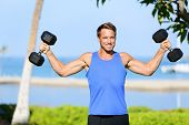 Weight training Fitness man with dumbbell weights in workout outside. Fit muscular male lifting weig