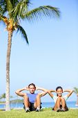 People training sit ups outside. Fitness couple doing situps exercise during outdoor cross training