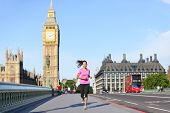 London lifestyle woman running near Big Ben. Female runner jogging training in city with red double