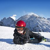 Young boy lying down in the snow, with his skis on, on a bright sunny day in the mountains,