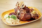 Crispy pork knuckle with sauerkraut and baked potato