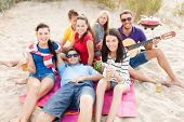 summer, holidays, vacation, music, happy people concept - group of friends with guitar having fun on
