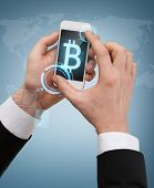 business, internet and technology concept - businessman touching screen of smartphone with bitcoin sign on screen