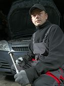 Auto mechanic posing with socket wrench in front of a car with raised hood