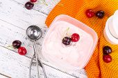 Ice cream in container and ice cream spoon on wooden table close-up