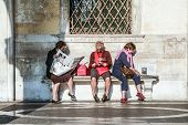 Women Sit At A Bench And Read Newspaper And Books