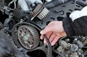 stock photo of overhauling  - Car mechanic replacing timing belt at camshaft of modern engine - JPG