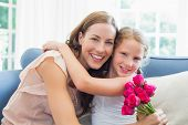 Portrait of a happy mother and daughter embracing with flowers in the living room at home