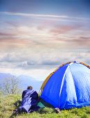 stock photo of sleeping bag  - Man lie in sleeping bag near the tent - JPG