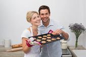 Portrait of happy young couple with freshly baked cookies in the kitchen at home