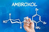 Hand with pen drawing the chemical formula of ambroxol