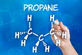 Hand with pen drawing the chemical formula of propane