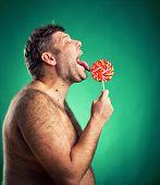 Shirtless man licking candy