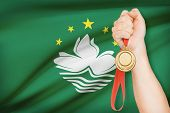 Medal In Hand With Flag On Background - Macao Special Administrative Region Of The People's Republic