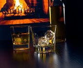 foto of whiskey  - glasses of whiskey with ice cubes near whiskey bottle in front of the fireplace at night - JPG