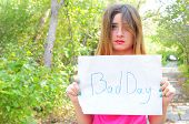 Cute girl hold on paper on which is written a bad day