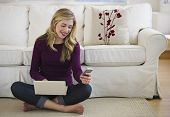 Female In Livingroom With Laptop And Cell Phone