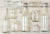 High angle shot of assorted glass bottles on a whitewashed wooden table. Clear glass bottles and con